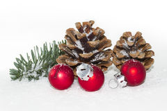 Red christmas balls with pinecones and snow Royalty Free Stock Images