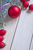 Red christmas balls and pinetree branch on white old painted woo Royalty Free Stock Photos
