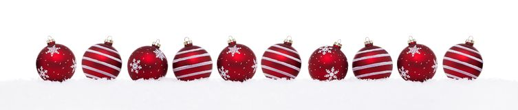 Red christmas balls in a row isolated on snow royalty free stock images