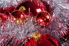 Red Christmas balls and shine tinsel. Christmas decorations closeup. Red Christmas balls and tinsel royalty free stock image