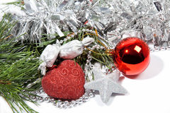 Red Christmas balls and silver star on pine branch Stock Photo