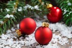 Red Christmas balls in the snow and spruce branches Stock Photos