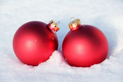 Red Christmas Balls in the Snow. Two red Christmas balls in fresh snow Stock Images
