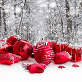 Red christmas balls in snowed forest Stock Images