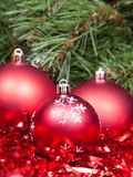 Red Christmas balls, tinsel close up and Xmas tree Royalty Free Stock Image