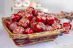 Red Christmas balls in wicker basket. Hand painted with traditional Croatian  decorations Royalty Free Stock Images