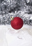Red Christmas Bauble. A red christmas bauble with tinsel in the background Stock Photo