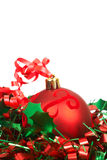 Red Christmas bauble. Single red Christmas bauble on green holy leaf tinsel Stock Photos