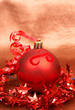 Red Christmas bauble. Single red Christmas bauble with star tinsel on golden silk background Stock Photography