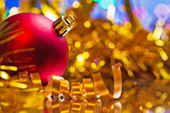 Red christmas bauble on background of blurred tinsel Royalty Free Stock Photos
