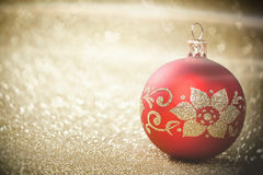 Red Christmas bauble on background of defocused golden lights. Royalty Free Stock Photography