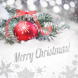 Red Christmas bauble and a caption. Red Christmas bauble on a neutral winter background with a caption Merry Christmas stock photography