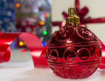 Red christmas bauble. Close up red bauble with lights and gifts royalty free stock image