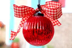 Red christmas bauble. Close up of shining red christmas bauble with red and white material bow on top, it is hanging in a window and the colourful back ground is Royalty Free Stock Photos