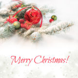 Red Christmas bauble on decorated fir twigs in snow, caption Stock Photo
