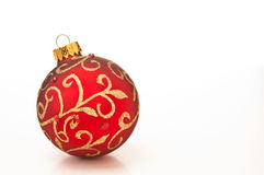 Red Christmas bauble. Decoration with gold leaf design on white background Stock Image