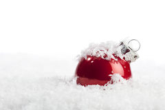 Red Christmas bauble in decorative snow Stock Photos