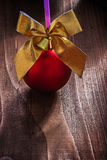 Red christmas bauble and gold colored bow with small bell on old Stock Photo