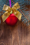 Red christmas bauble and gold colored bow with small bell on old Stock Photos