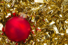 Red christmas bauble on gold tinsel Stock Photography