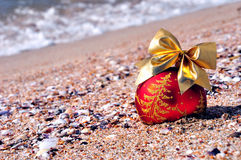 Red christmas bauble with golden bow on the sand Stock Image