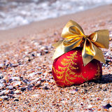 Red christmas bauble with golden bow on the sand Royalty Free Stock Photography
