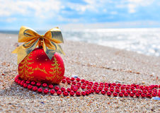 Red christmas bauble with golden bow on the sand Stock Photography