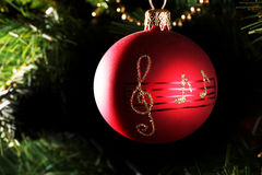 A red christmas bauble with musical notes. A close up of a red christmas bauble with musical notes Stock Photography
