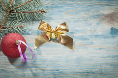 Red Christmas bauble pine brunch golden bow on wooden board holi Royalty Free Stock Photos