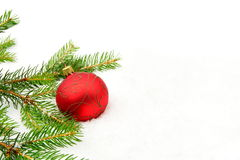 Red christmas bauble with red star and needles fir on snow Royalty Free Stock Images