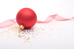 Red Christmas bauble and ribbon. Red bauble with gold stars and red ribbon on a white background Stock Photos
