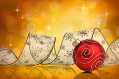 Red christmas bauble with ribbon. In front of a abstract bokeh background with lights and stars Stock Images