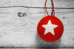 Red Christmas bauble on a rustic wood background. Red Christmas bauble decorated with a white star hanging on a rustic wood background with copyspace for your stock images