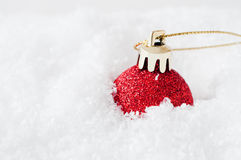 Red Christmas Bauble in Snow. A sparkly red glitter Christmas bauble, with gold clasp and gilt string, sunk into fake white snow to the right of frame. Snow royalty free stock photo