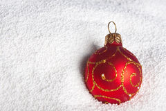 Red Christmas bauble on to snow. Stock Photo