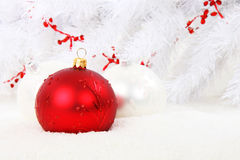 Red Christmas bauble with white balls in snow. Red christmas bauble with white christmas balls and white tree in the Royalty Free Stock Photo