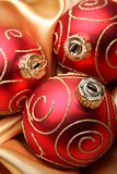 Red christmas baubles. Three red christmas baubles on golden silk Stock Photography