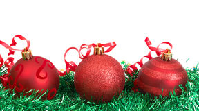 Red Christmas baubles. Three red Christmas baubles on green tinsel Royalty Free Stock Image