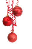 Red Christmas baubles. Three red Christmas baubles hanging on a ribbon on white background with copy space Stock Images