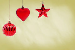 RED CHRISTMAS BAUBLES. Hanging red christmas baubles on gold background Stock Photo