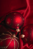 Red Christmas baubles. Or balls on silky background with copy space Royalty Free Stock Photography