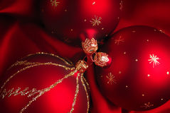 Red Christmas baubles. Background of red Christmas balls or bauble decorations on silky background Stock Photography