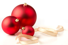 Red Christmas baubles & gold ribbons. Red christmas baubles and gold ribbons on a white background Stock Photos