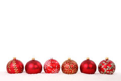Red christmas baubles in line isolated. Red christmas baubles in line in snow isolated on white background Royalty Free Stock Images