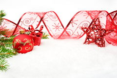 Red christmas baubles with red star and needles fir and ribbon o Royalty Free Stock Photography