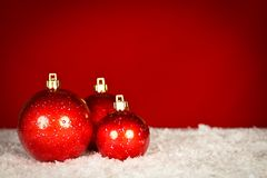 Red Christmas baubles on snow. With red background, studio shot Stock Photography