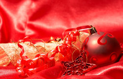Red Christmas baubles and star. On red silk background with copy space Stock Photo