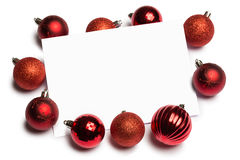 Red christmas baubles surrounding white page Stock Photos