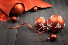 Red Christmas baubles tied with ribbon and red napkin on wood. En table Stock Images