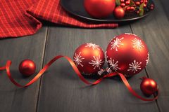 Red Christmas baubles tied with ribbon and red napkin on wood. En table Stock Photography